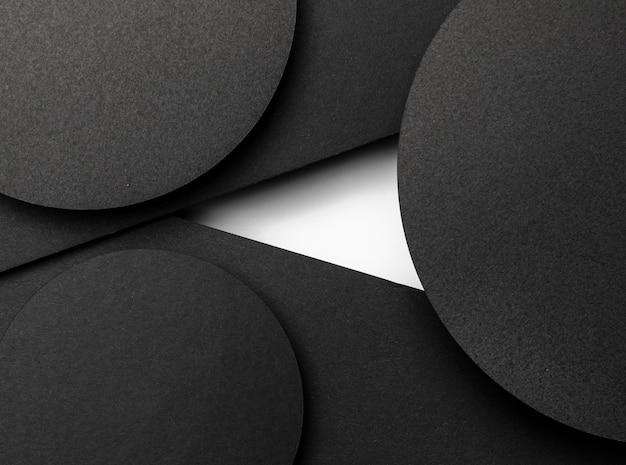 Zwarte cirkelvormige lagen papier en witte vlek Gratis Foto