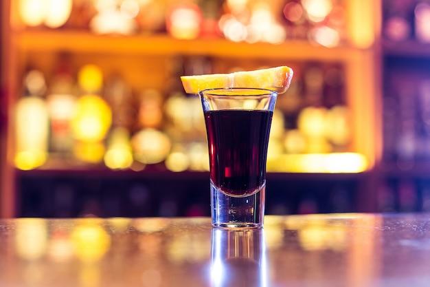 Zwarte cocktail in een stapel met een schijfje sinaasappel Premium Foto