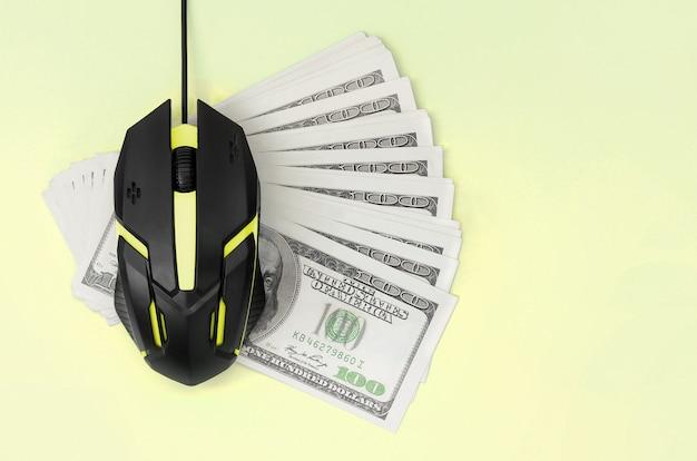 Zwarte computermuis op vele honderd dollarbiljetten Premium Foto