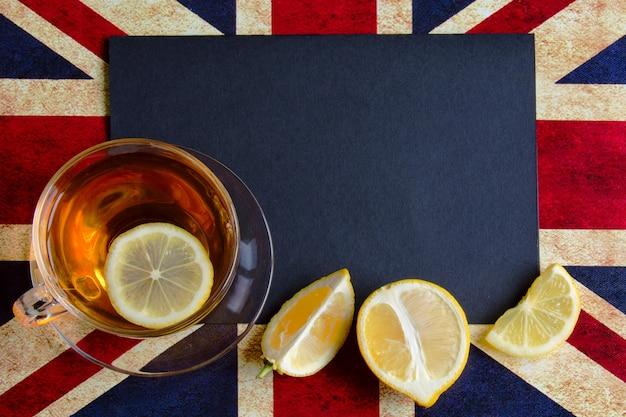 Zwarte copyspace van britse vlag met een kopje citroenthee Premium Foto