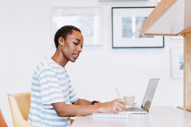 Zwarte dame die een aantekening maakt tijdens een vergadering Premium Foto
