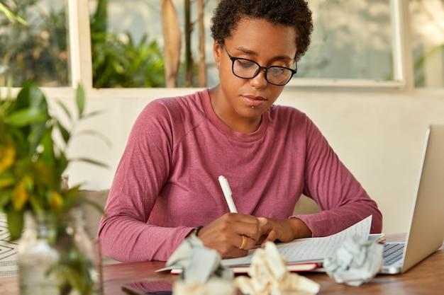 Zwarte dame maakt publicatie, schrijft records in kladblok, gericht op schrijven, gebruikt laptop voor het zoeken naar informatie op internet, zit op de werkplek met verfrommeld papier maakt testonderzoek Gratis Foto