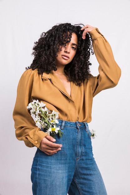 Zwarte die zich met madeliefjebloemen in jeanszak bevindt Gratis Foto