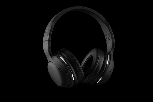Zwarte draadloze hoofdtelefoons die op een zwarte achtergrond worden geïsoleerd. Premium Foto