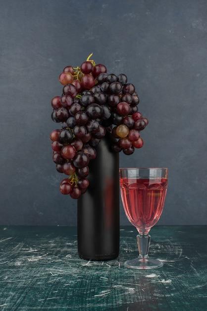 Zwarte druiven rond een fles en een glas wijn op marmeren tafel. Gratis Foto