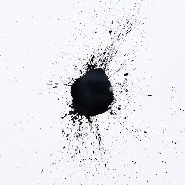 Zwarte druppel spatten op wit Premium Foto