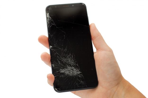 Zwarte gebroken telefoon in de hand op wit gebarsten touchscreen Premium Foto