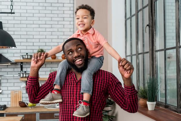 Zwarte gelukkige vader die zoon op schouders vervoert Gratis Foto