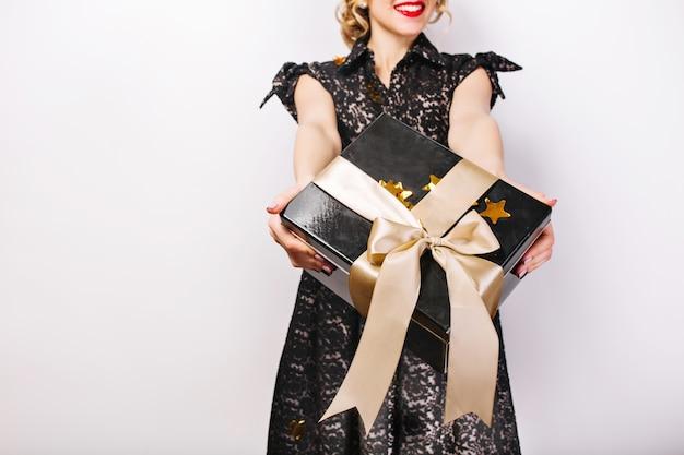 Zwarte geschenkdoos in haar handen, rode lippen, zwarte jurk, verrassingsemotie. Gratis Foto
