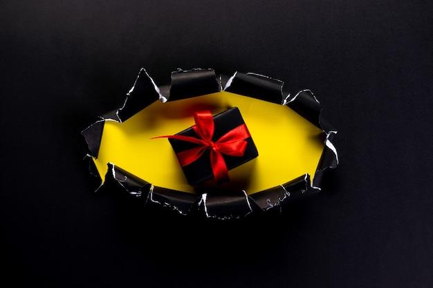 Zwarte geschenkdoos met rood lint Premium Foto