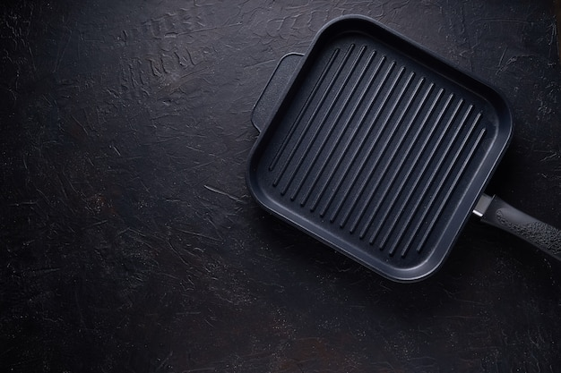 Zwarte grillpan op donkere steen hoogste mening als achtergrond Premium Foto