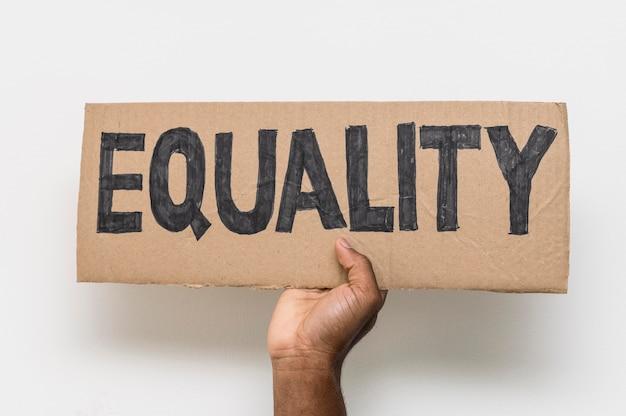 Zwarte hand met gelijkheid op karton Gratis Foto
