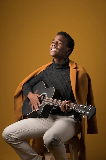 Zwarte jongen die de gitaar speelt Gratis Foto