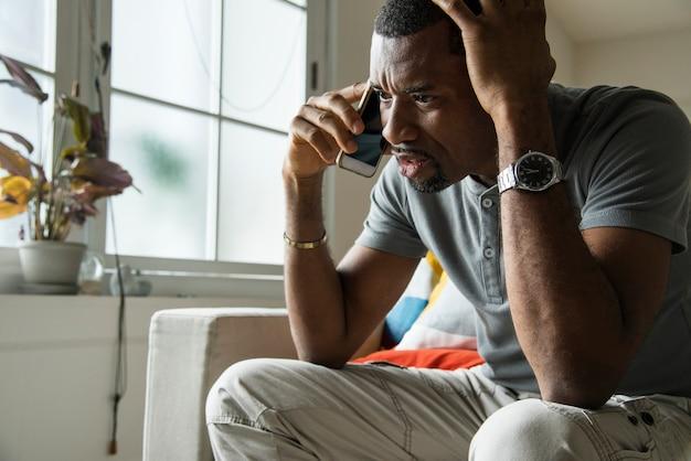 Zwarte kerel sprekende telefoon met boze emotie Premium Foto