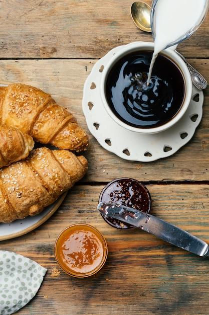 Zwarte koffie en croissants met jam. typisch frans ontbijt (petit déjeuner) Premium Foto