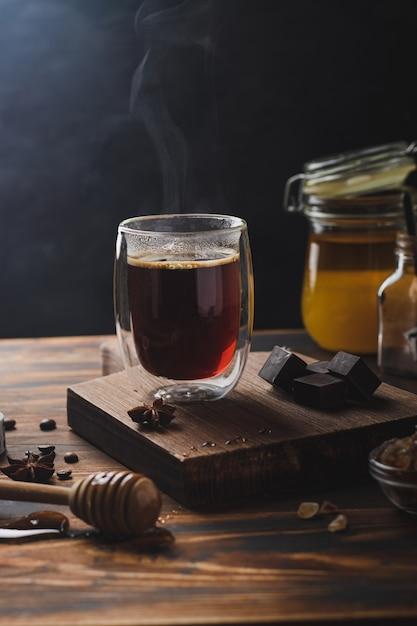 Zwarte koffie in het glas met stoom over houten oppervlak, honing en donkere chocolade Premium Foto