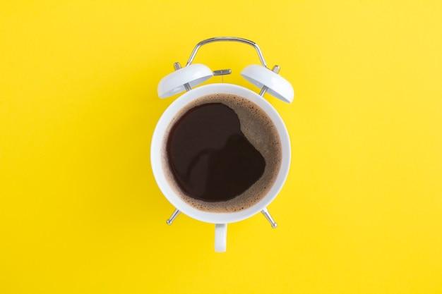 Zwarte koffie op de wijzerplaat van de witte wekker in het midden van de gele achtergrond Premium Foto