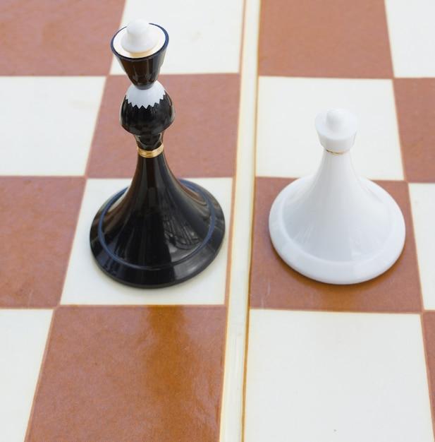 Zwarte koningin en witte pion op schaakbord Premium Foto