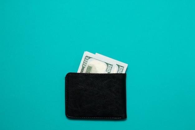 Zwarte lederen portefeuille met dollarbiljetten op blauwe achtergrond. heren portemonnee met geldwissels Premium Foto