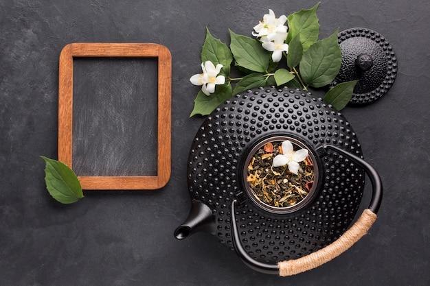 Zwarte lege lei met droog theeingrediënt op zwarte achtergrond Gratis Foto