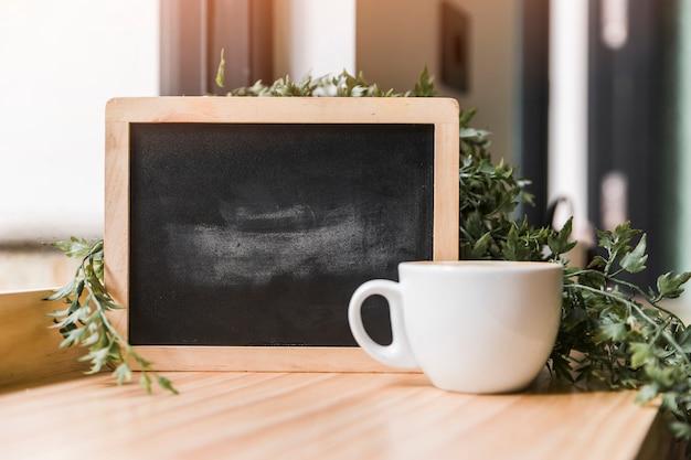 Zwarte lei met kopje koffie op houten bureau Gratis Foto