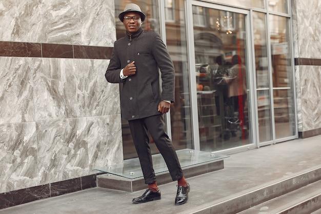 Zwarte man in een zwarte jas in een herfst stad Gratis Foto