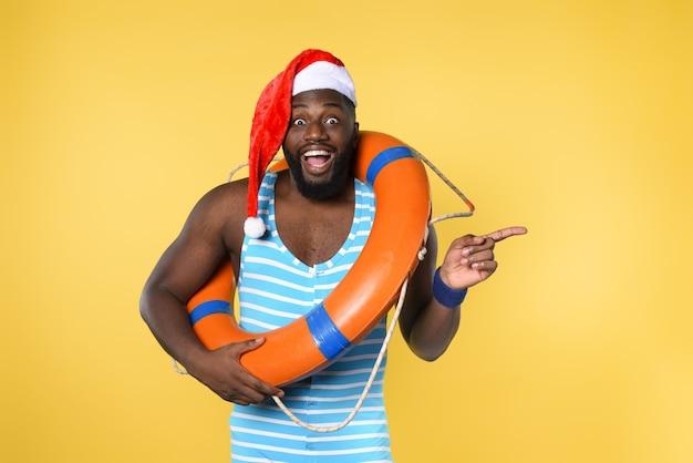 Zwarte man in zwembroek klaar om te gaan op een zonnige plek voor kerstmis. gele muur Premium Foto