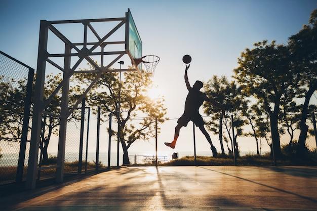 Zwarte man sporten, basketbal spelen op zonsopgang, silhouet springen Gratis Foto