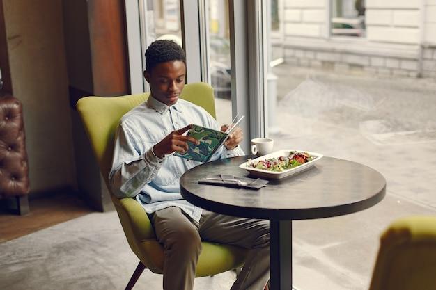 Zwarte man zit in een cafe en het eten van een groente salade Gratis Foto