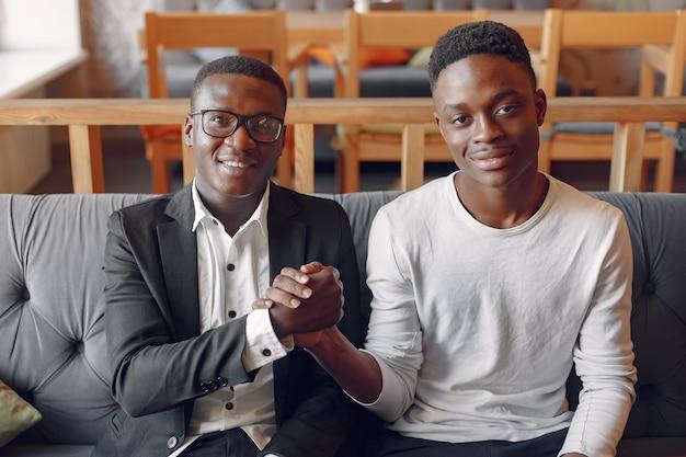Zwarte mannen in een café met een bedrijf Gratis Foto