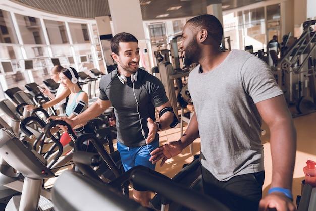 Zwarte mens die in de gymnastiek met een vriend uitoefent. Premium Foto