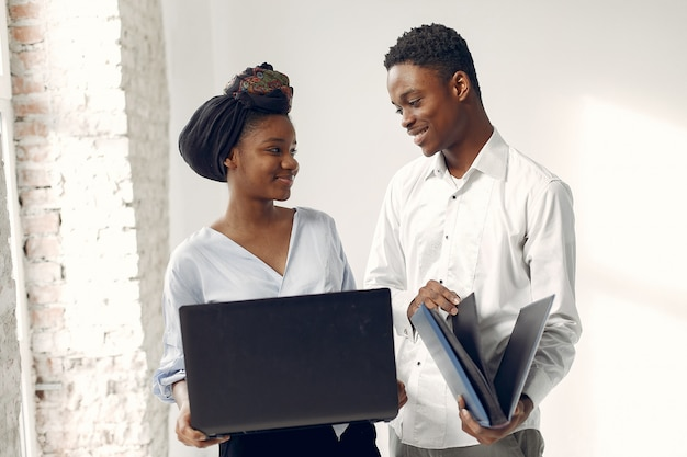 Zwarte mensen die zich op een witte muur met laptop bevinden Gratis Foto
