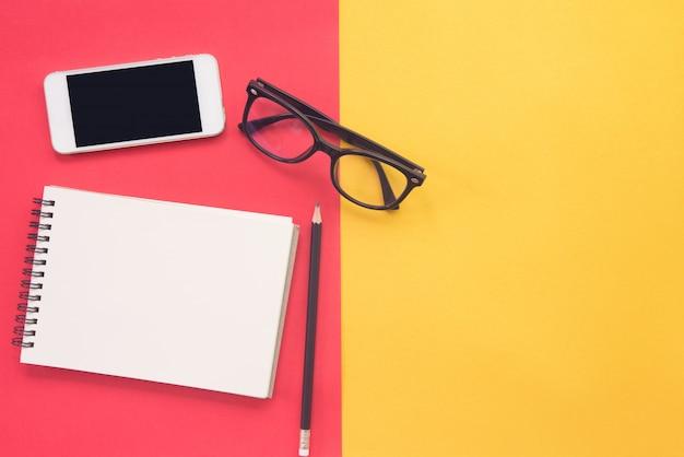 Zwarte moderne oogglazen, smartphone en leeg notitieboekje op rood en geel. Premium Foto