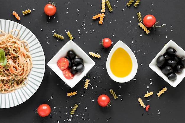 Zwarte olijven; olie; cherry tomaat en smakelijke spaghetti pasta gerangschikt over zwarte achtergrond Gratis Foto
