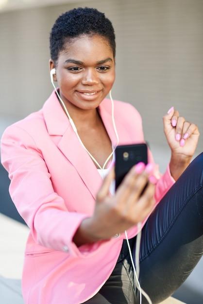 Zwarte onderneemsterzitting die in openlucht via videoconferentie met haar smartphone spreekt. Premium Foto