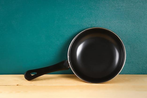 Zwarte pan op een houten plank. keukengerei. Premium Foto
