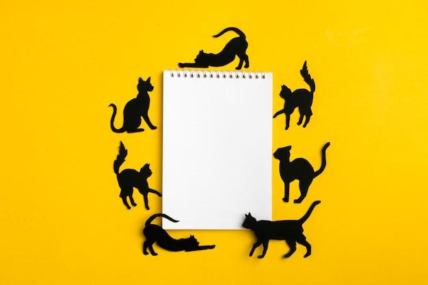 Zwarte papieren katten en een notitieboekje Premium Foto