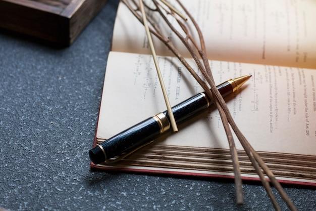 Zwarte pen, gedroogde bloemen en boek op donkere achtergrond Premium Foto