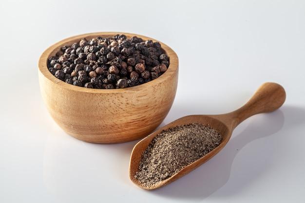 Zwarte peper en pepermolen op een witte achtergrond Premium Foto
