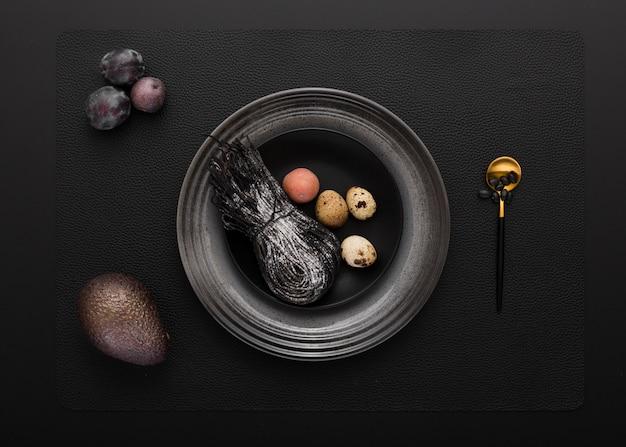 Zwarte plaat met zwarte pasta en kwartel eieren op een donkere achtergrond Gratis Foto