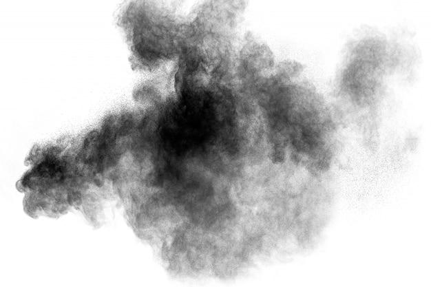 Zwarte poederexplosie tegen witte achtergrond. houtskoolstofdeeltjes wolkelen in de lucht. Premium Foto