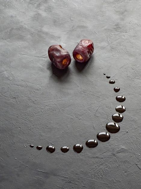 Zwarte ramadan achtergrond met datums en datums siroop gegoten in de vorm van een halve maan. Premium Foto