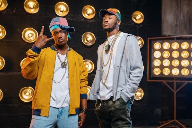 Zwarte rappers in caps op het podium met schijnwerpers Premium Foto