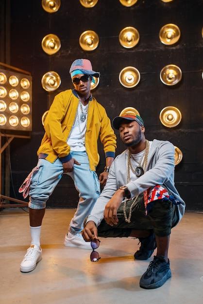Zwarte rappers in petten dansen op het podium met schijnwerpers Premium Foto