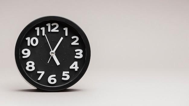 Zwarte ronde wekker tegen grijze achtergrond Gratis Foto