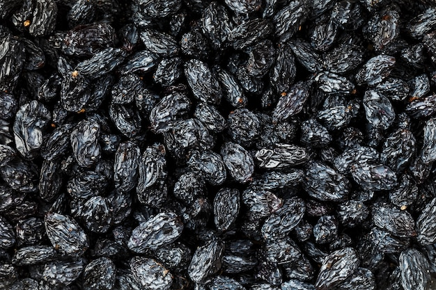 Zwarte rozijnentextuur, populair gedroogd fruit. gedroogde druiven. Premium Foto