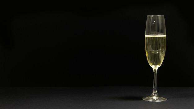 Zwarte scène met een glas champagne. Gratis Foto