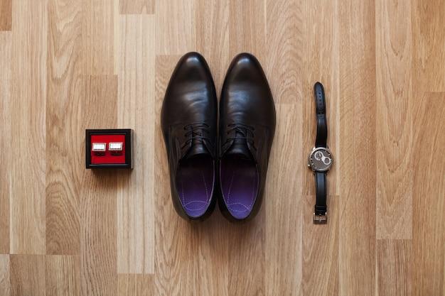 Zwarte schoenen, horloge en manchetknopen op de vloer. accessoires voor de bruidegom op de trouwdag. Premium Foto