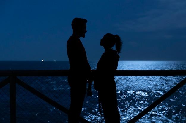Zwarte silhouetten van een verliefde paar kijken naar elkaar Gratis Foto