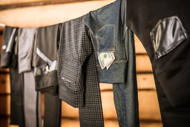 Zwarte stijlvolle damesbroeken en jeans hangen aan touw in de kledingkast. Premium Foto